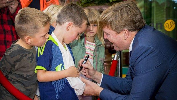 Koning Willem-Alexander zet spontaan handtekening op gips